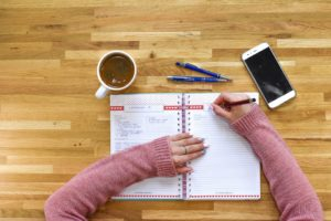 Girl writing about moving from house to NYC apartment in notebook
