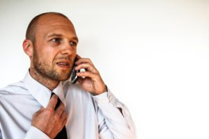 A man in a shirt and tie, calling to file a property damage claim.