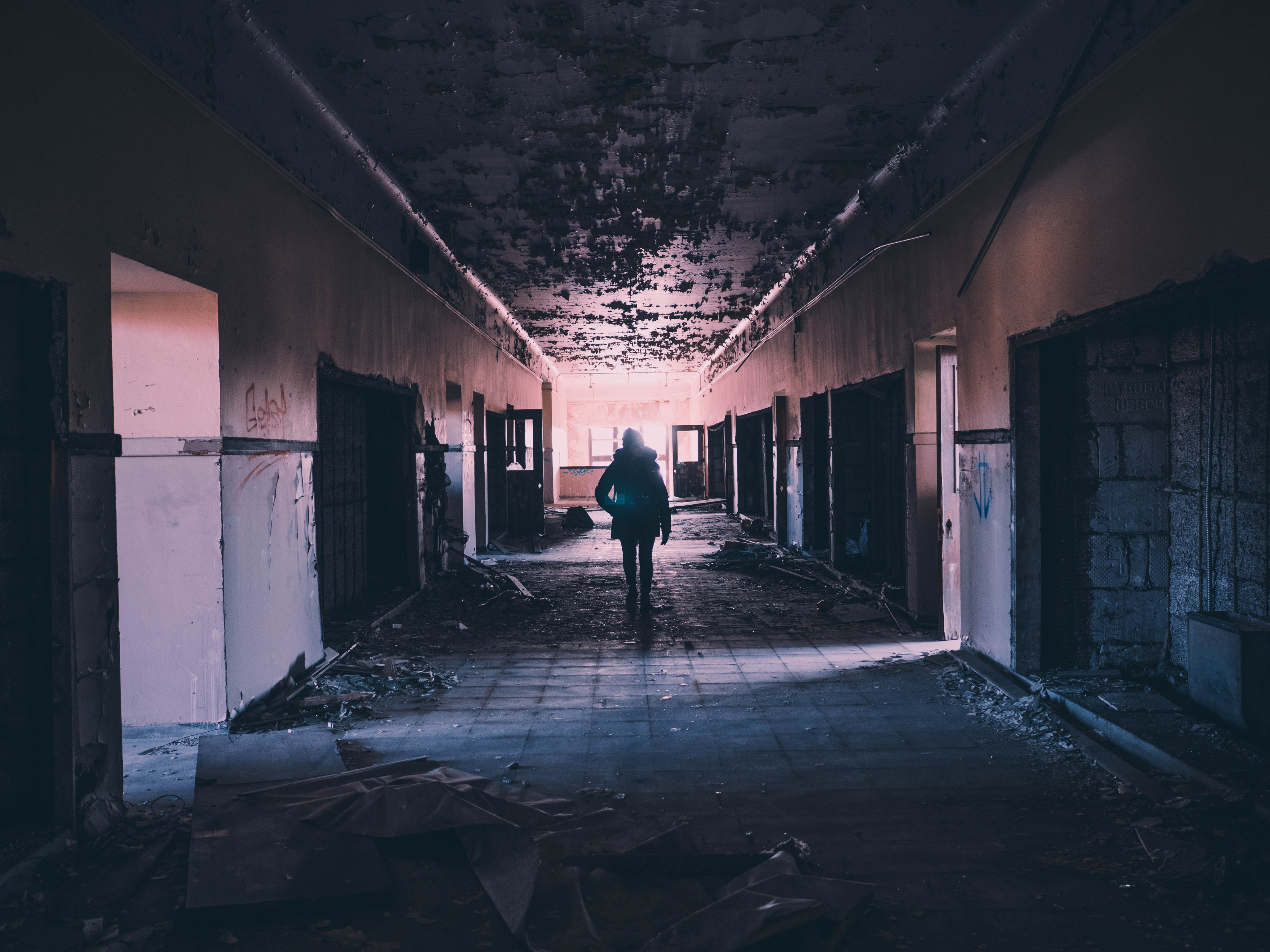A woman walking down a burnt and damaged hallway.