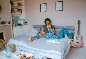Couple on the bed eating pizza
