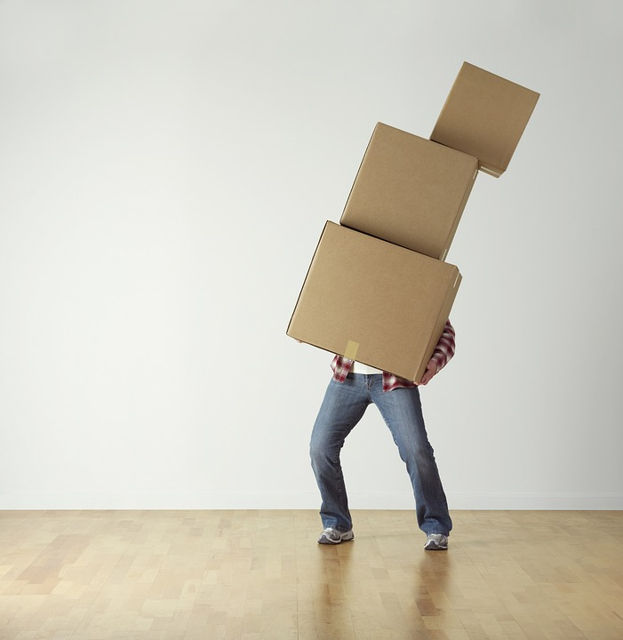 A man carrying a large number of boxes.