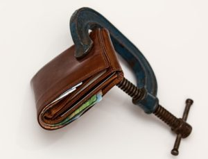A wallet that is being squeezed - as a way to save money for your down payment