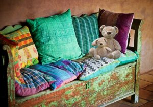 Old sofa with pillows and toys on.