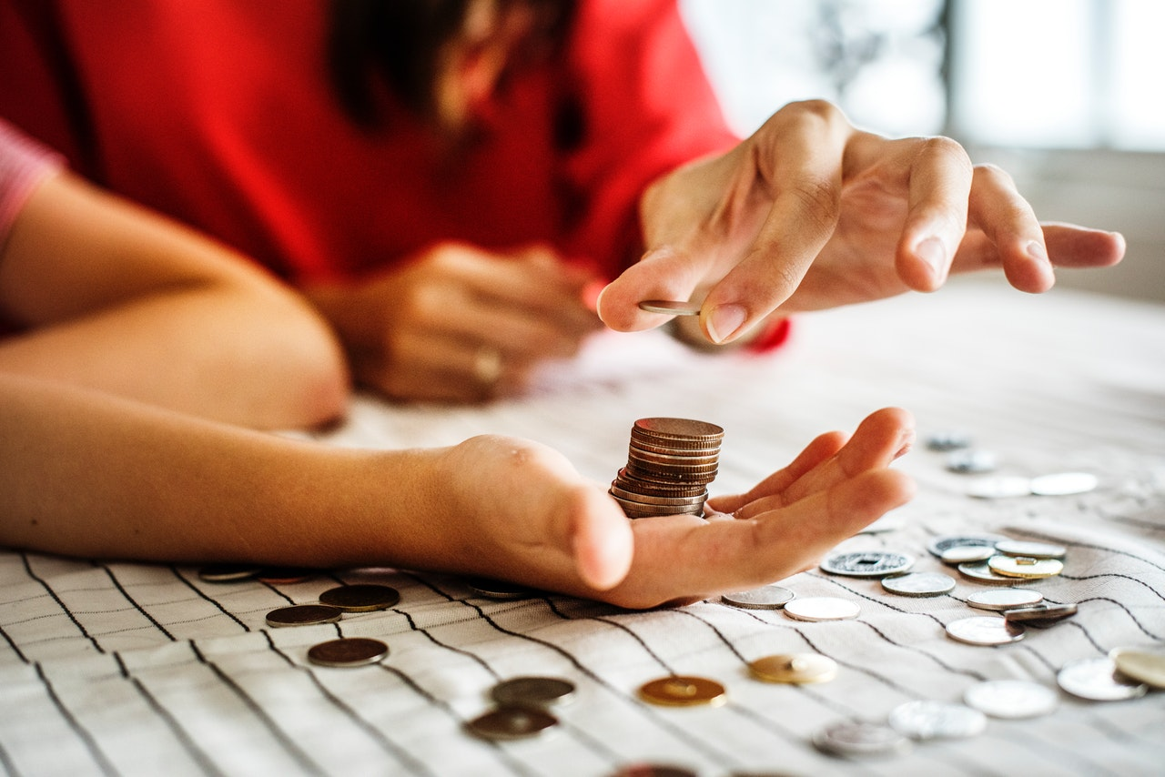 A person putting coins in a hand