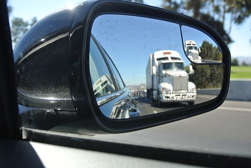 baby boomers housing - a moving truck in a mirror.