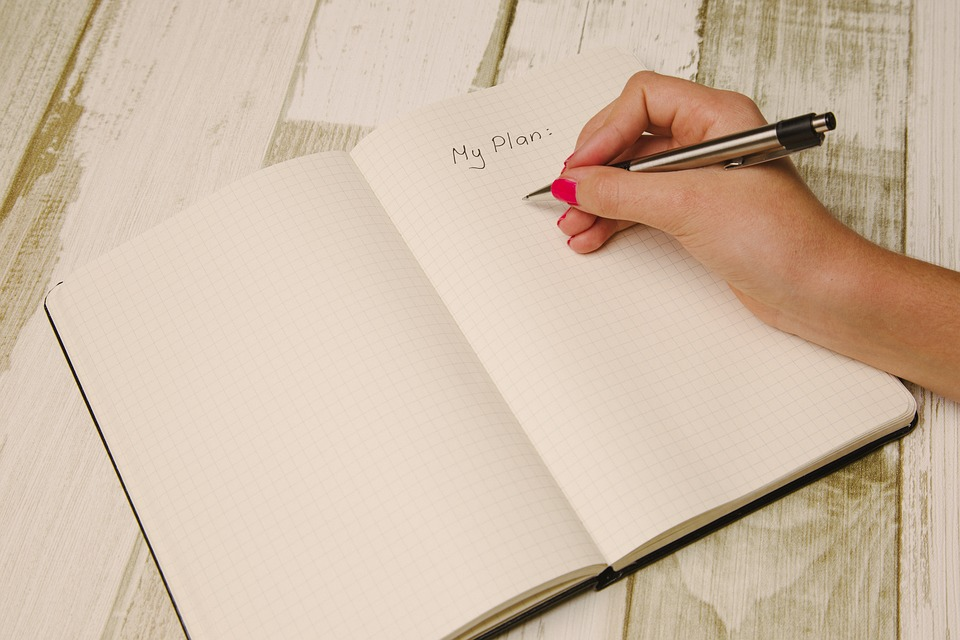 an open noutbook and a girl trying to make a moving plan
