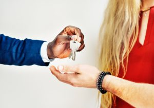 A person handing house keys to another person who's done house hunting in Oxford