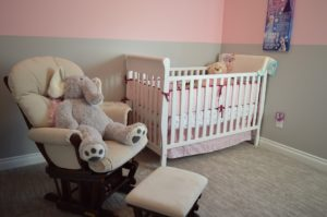 A light pink nursery with a big stuffed elephant sitting in a chair.