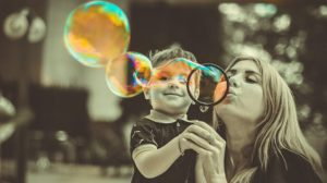 A kid and its mother blowing bubbles.