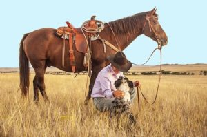 A cowboy with a horse and a dog in the filed.