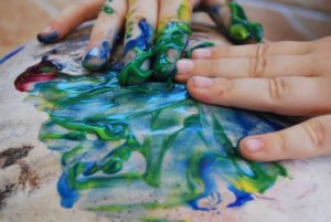 Kids hand painting as a great way to reuse moving boxes.