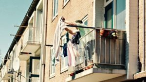 There is a person, standing on a terrace and hanging some clothes.