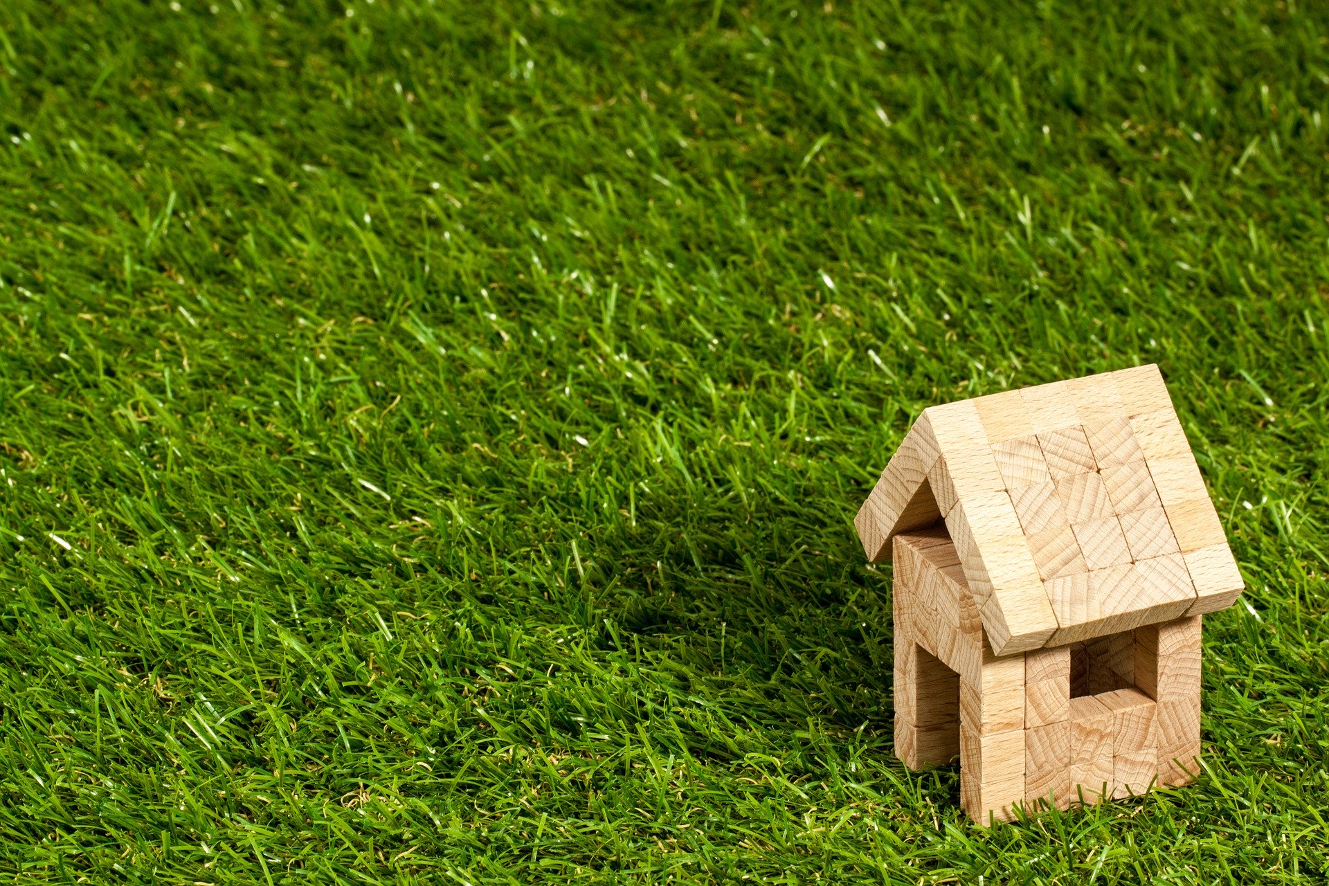 A small wooden model house on the grass.