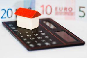 a calculator and a house figurine