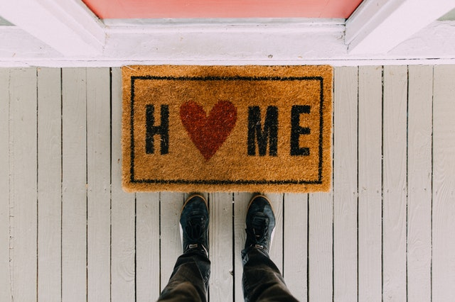 There is a brown doormat with the inscription 'HOME' on it, and there is a person standing next to it.