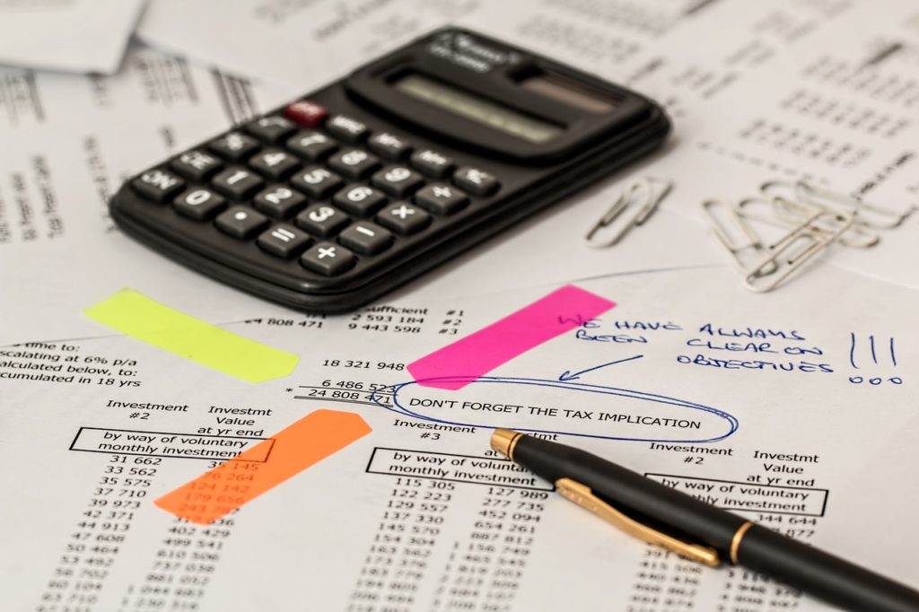 A tax paper and a calculator to calculate the unexpected Florida first-time home buyer costs.
