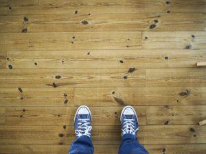 Person standing on a hardwood floor.