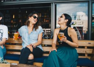 Two friends laughing and having drinks