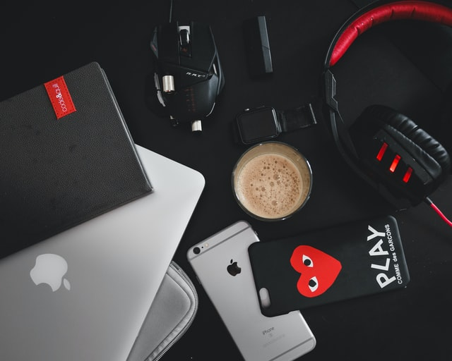 A mobile phone, tablet, coffee, and headphones on the table