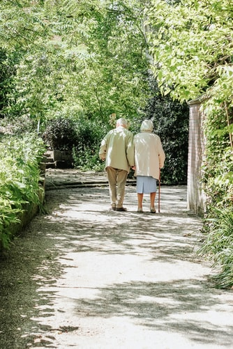 An elderly couple walking and discussing possible home-buying benefits for seniors.