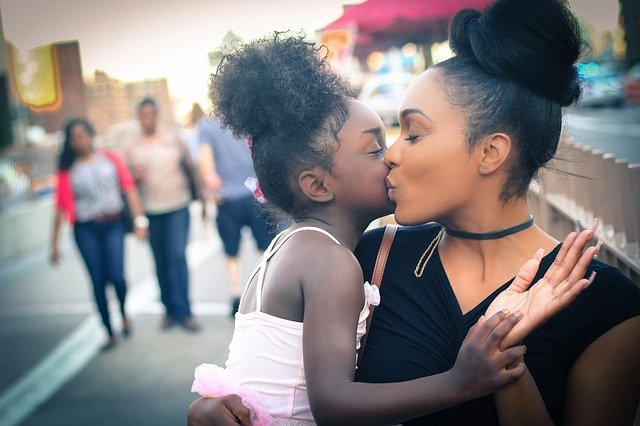 A mother kissing her daughter in a street of one of family-friendly cities of Westchester Country.