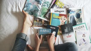 A person exploring some books on the bed as you will do once you decide to prepare your books for an international relocation.