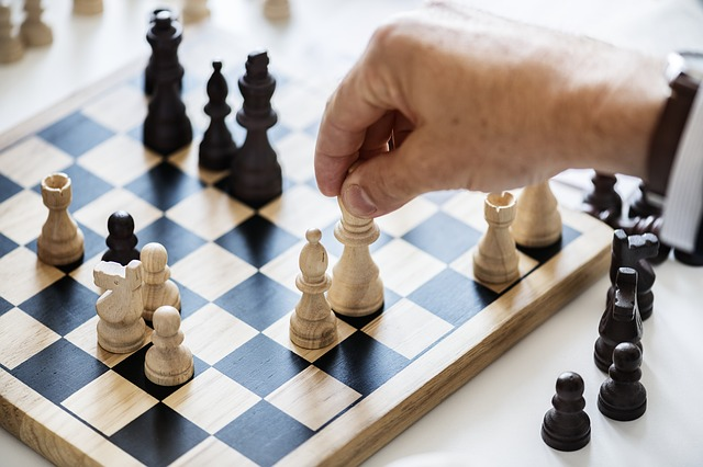 A man playing chess considering strategy for business relocation