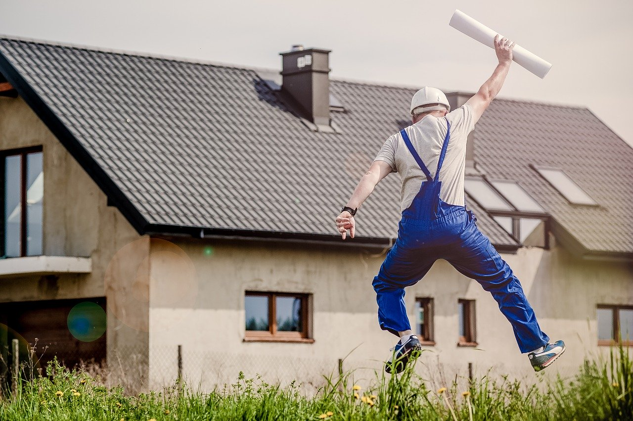 An architect with a project in his hand jumping with happiness.