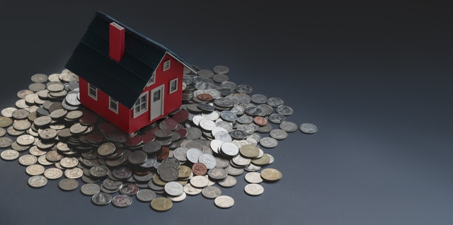 Miniature house on top of a pile of coins.