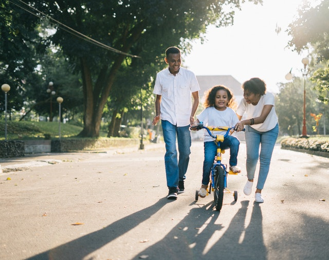 Parents teaching their child to ride a bicycle in one of the most family-friendly suburbs in Ontario.