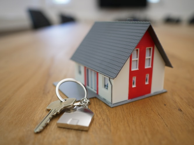 Keys to a home linked to a keychain shaped as a small house.