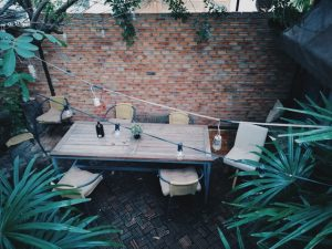 A patio with a table, six chairs, and palm trees